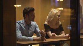 坐在餐馆和挥动与白肤金发的妇女,关系的英俊的人 股票录像