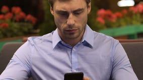坐在餐馆和看手机的商人,检查邮件 影视素材