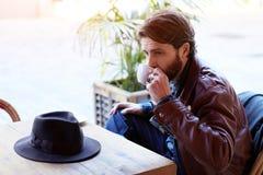 坐在餐馆和等待忘记了他的帽子的朋友的英俊的人 免版税库存照片