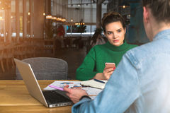 坐在餐馆和谈话的桌上的两个年轻女商人 在桌上是膝上型计算机,笔记本,纸图 库存照片