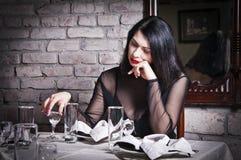 坐在餐馆桌上的孤独的女孩 库存图片