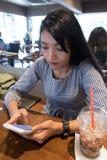 坐在餐馆的年轻女人 免版税库存照片