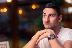 坐在餐馆的惊奇的年轻人 免版税库存照片