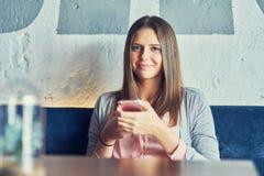 坐在餐馆的成人俏丽的妇女 图库摄影