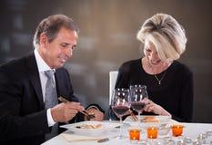 坐在餐馆的成熟夫妇 免版税库存照片