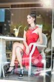 坐在餐馆的红色礼服的时兴的可爱的少妇,在窗口之外 美好深色摆在餐馆 库存照片