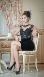 坐在餐馆的黑礼服的时兴的可爱的少妇 美好深色摆在典雅的葡萄酒风景 免版税库存图片