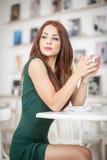 坐在餐馆的绿色礼服的时兴的可爱的少妇 摆在典雅的风景的美丽的红头发人用咖啡 免版税图库摄影