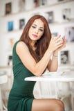 坐在餐馆的绿色礼服的时兴的可爱的少妇 摆在典雅的风景的美丽的红头发人用咖啡 免版税库存图片