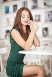 坐在餐馆的绿色礼服的时兴的可爱的少妇 摆在典雅的风景的美丽的红头发人用咖啡 库存图片