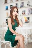 坐在餐馆的绿色礼服的时兴的可爱的少妇 摆在典雅的风景的美丽的红头发人用汁液 库存照片