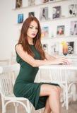 坐在餐馆的绿色礼服的时兴的可爱的少妇 摆在典雅的风景的美丽的红头发人用汁液 免版税库存图片