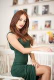 坐在餐馆的绿色礼服的时兴的可爱的少妇 免版税库存图片