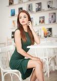 坐在餐馆的绿色礼服的时兴的可爱的少妇 库存照片