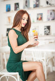 坐在餐馆的绿色礼服的时兴的可爱的少妇 免版税图库摄影