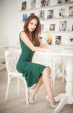 坐在餐馆的绿色礼服的时兴的可爱的少妇 免版税库存照片