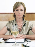 坐在餐馆表上的女实业家 免版税库存图片