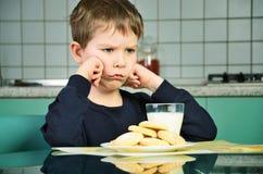 坐在饭桌上的恼怒的小男孩 水平 库存图片