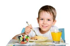 坐在饭桌和看上的微笑的快乐的男孩Th 免版税图库摄影