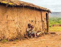 坐在马塞人部落村庄房子前面的两个男孩 免版税库存图片