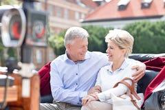 坐在马推车的浪漫中年夫妇 免版税库存图片