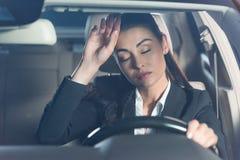 坐在驾驶席和接触的衣服的年轻疲乏的妇女 库存图片