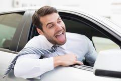坐在驾驶席的无忧无虑的商人 免版税库存照片