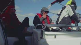 坐在驾驶舱和谈话内的驾游艇者的慢动作 股票录像