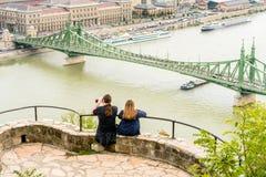 坐在高为照相的自由桥梁的一个观点的一对年轻夫妇在多瑙河,布达佩斯 免版税库存图片