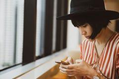 坐在高大厦的年轻亚裔妇女,使用智能手机 免版税图库摄影
