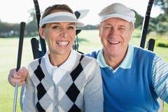 坐在高尔夫球多虫微笑的愉快的打高尔夫球的夫妇对照相机 免版税库存照片