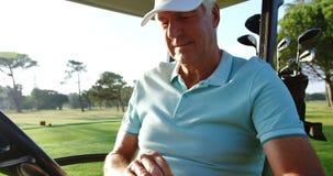 坐在高尔夫球多虫的佩带的高尔夫球手套的高尔夫球运动员 股票录像
