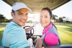 坐在高尔夫球的快乐的高尔夫球运动员夫妇bugggy 免版税库存图片