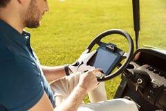 坐在高尔夫车的一位男性高尔夫球运动员的播种的图象 免版税库存图片