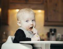 坐在高脚椅子所有杂乱吃橙色婴儿食品与的婴孩 免版税库存图片