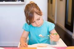 坐在高脚椅子的小孩吃与匙子的蛋糕 免版税库存图片