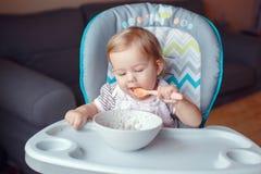 坐在高脚椅子的白种人儿童孩子女孩吃与匙子的谷物 库存照片