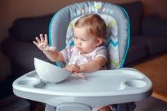 坐在高脚椅子的白种人儿童孩子女孩吃与匙子的谷物 免版税库存照片