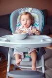 坐在高脚椅子的白种人儿童孩子女孩吃与匙子的谷物 免版税图库摄影