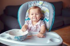 坐在高脚椅子的白种人儿童孩子女孩吃与匙子的谷物 免版税库存图片