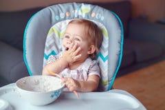 坐在高脚椅子的白种人儿童孩子女孩吃与匙子的谷物 库存图片