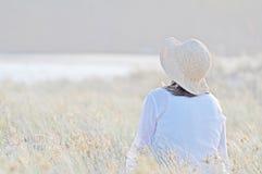 坐在高长的草的浪漫妇女 免版税库存照片