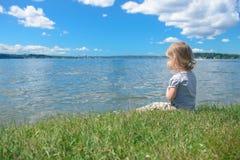 坐在鲜绿色的草的小女孩在湖附近 免版税库存图片