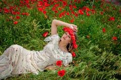 坐在鸦片花的美丽的妇女 免版税库存照片