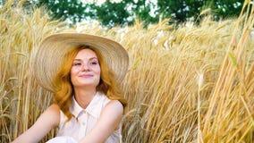 坐在麦田的快乐的年轻红发妇女画象在夏天 股票录像
