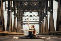 坐在麻线姿势的芭蕾舞女演员在路和路轨在金属支持旁边 免版税库存图片