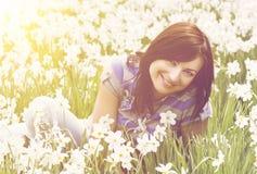 坐在黄水仙中的微笑的少妇 库存图片
