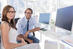 坐在他们书桌和微笑的设计师 免版税图库摄影