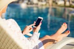 坐在轻便折叠躺椅和使用手机的妇女 库存图片
