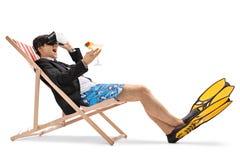 坐在轻便折叠躺椅和使用VR耳机的商人 库存照片